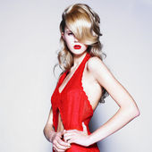 Young pretty blond woman in a fashionable red dress — Foto Stock