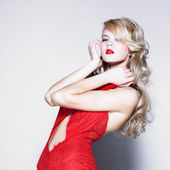 Young pretty blond woman in a fashionable red dress — Stock Photo