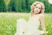 Femme en robe blanche, assis sur l'herbe — Photo