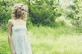Vacker blond tjej på gröna fält med blommor — Stockfoto