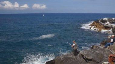 Homem pesca na costa rochosa do mar — Vídeo stock