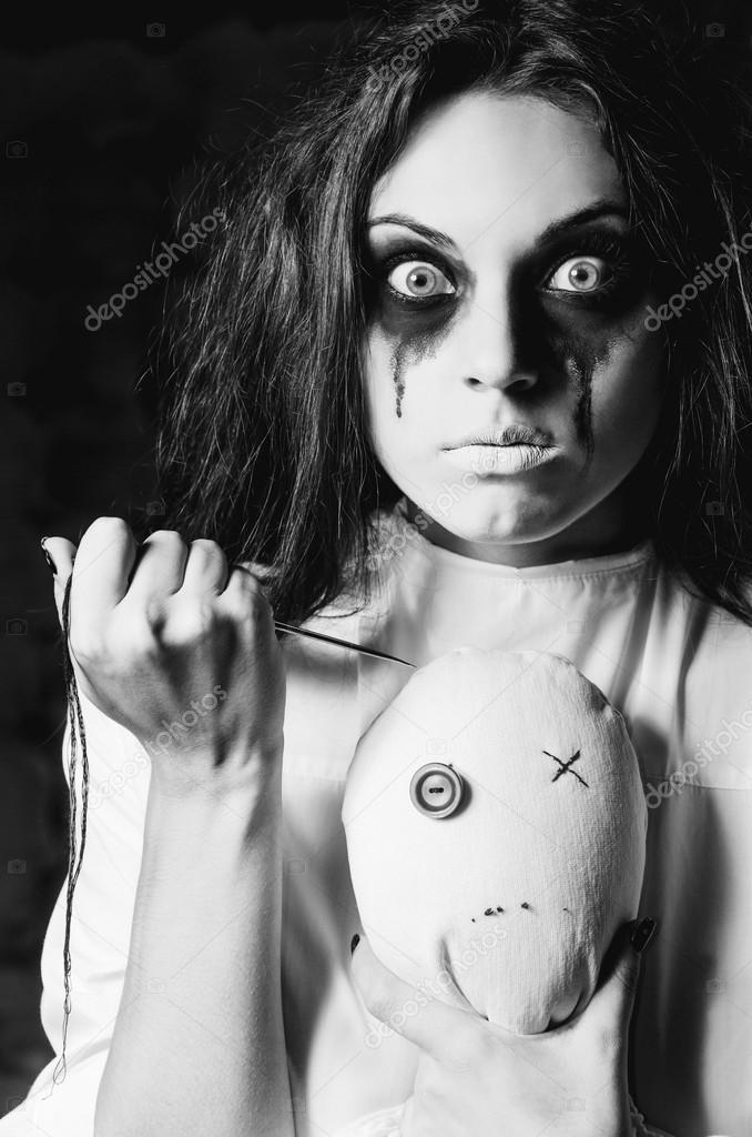 Horror scene the strange crazy girl with moppet doll and needle