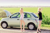 Two sexy blonde girls standing near their broken car and hitchhiking — Stock Photo