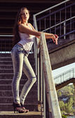 Beautiful young girl in shirt and jeans stands on stairs at sunset time — Stock Photo