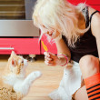 Beautiful blonde girl with candy in hand and cat sitting on kitchen floor — Stock Photo