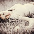 Sad beautiful girl lying on grass. Faded effect — Stock Photo