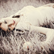 Sad beautiful girl lying on grass. Faded effect — Stock Photo #22389187
