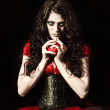 Strange scary girl with mouth sewn shut holds apple studded with nails — Stock Photo #22389189