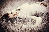 Sad beautiful girl lying on grass. Faded effect — Stock Photo