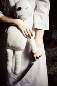 Horror style shot: moppet doll and knife in someone's hands — Stock Photo