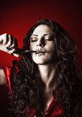 Horror shot: strange girl with mouth sewn shut cutting the thread — Stock Photo