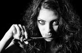 Horror shot: scary strange girl with mouth sewn shut cutting off the thread — Stock Photo