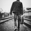 Young man with guitar case in hand is going away. Rear view, black and white — Stock Photo