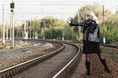 Beautiful young girl is hitchhiking on railroad. Rear view — Stock Photo