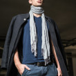 Fashion shot: handsome young man wearing jeans, coat, shirt and scarf — Stock Photo