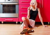 Beautiful blonde girl with candy in hand sits on kitchen floor — Stock Photo