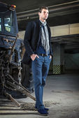 Fashion shot: handsome young man wearing jeans and coat against the tractor — Stock Photo