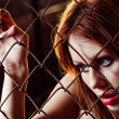 Closeup portrait of beautiful young girl behind metallic grid — Stock Photo #39236803