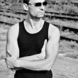 Fashion shot: portrait of handsome young man in black shirt wearing sunglasses. Black and white — Stock Photo