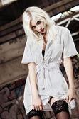 Beautiful strange nurse among industrial ruins — Stock Photo