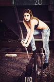 Beautiful young girl in bra and jeans pulls the railway lever — Stock Photo