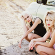 Two sad beautiful blonde girls sitting near broken car and waiting for help — Stock Photo