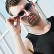Fashion shot: closeup portrait of handsome young man wearing sunglasses — Stock Photo #41911827