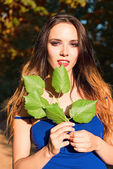 Beautiful young girl holding leaves in hands  — Foto de Stock