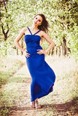 Beautiful young girl in blue dress among the trees — 图库照片