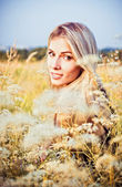 Beautiful smiling young girl sitting among the grass and flowers — Stok fotoğraf