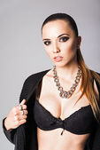 Fashion portrait of pretty young girl wearing black jacket, bra and necklace — Stock Photo