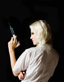 Beautiful young girl in the image of nurse with syringe in hand, rear view — Stock Photo