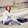 Beautiful young girl sitting on road — Stock Photo #43974183