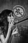 "Beautiful young woman lights cigarette near ""No fire and smoking"" sign — Stock Photo"