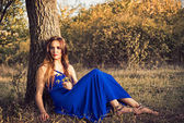 Beautiful young woman sitting under tree. Sunset time — Stockfoto