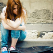 Beautiful young sad girl sitting on asphalt — Stock Photo #47713265