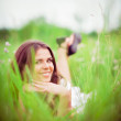 Happy smiling beautiful young woman lying among grass and flowers — Stock Photo #48036663