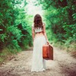 Young woman with suitcase in hand going away by rural road — Stock Photo #48036667