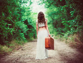 Young woman with suitcase in hand going away by rural road — Stock Photo