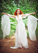 Beautiful redhead woman wearing white dress in a garden — Stock Photo