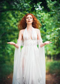 Gorgeous red-haired woman wearing white dress in a garden — Foto de Stock