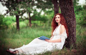 Lovely redhead woman sitting under tree and reading a book — Stock Photo