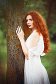 Beautiful redhead woman wearing white dress stands near tree — Foto Stock