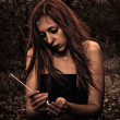 Beautiful young sad girl with match in hands — Stock Photo #7845391