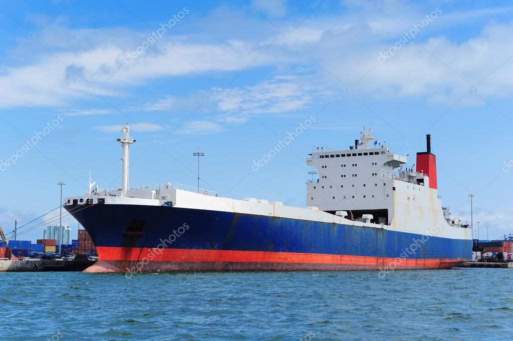 Cargo ship at Miami harbor with crane and blue sky over sea.  Stock Photo #13183702