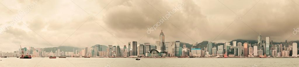 Urban architecture in Hong Kong Victoria Harbor with city skyline and cloud in the day with yellow tone.  Stock Photo #13506307
