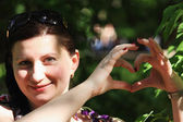 緑色の背景で女の子表示ハートマークの肖像画 — ストック写真