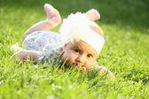 Adorable baby girl lying on green summer grass — Stock Photo