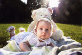 Adorable baby girl lying on green summer lawn — Stock Photo