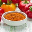 Ground paprika in a white china bowl and fresh pepper — Stockfoto